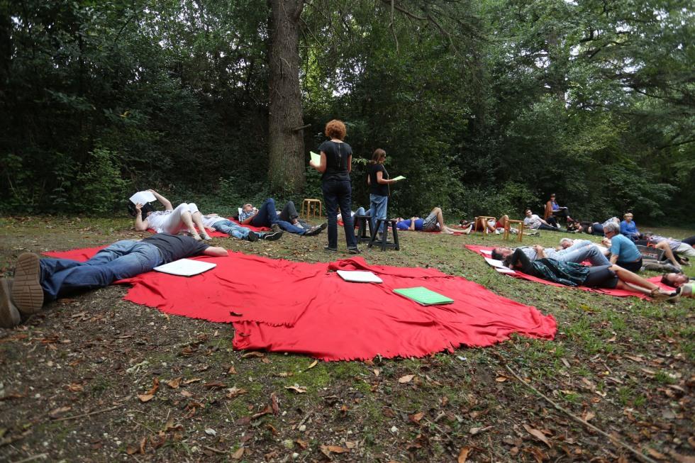 Les 2 lectrices de Nous verrons mieux pendant le RDV du dimanche dans la forêt de Bassens. Allongés dans l'herbe, les gens écoutent l'histoire…